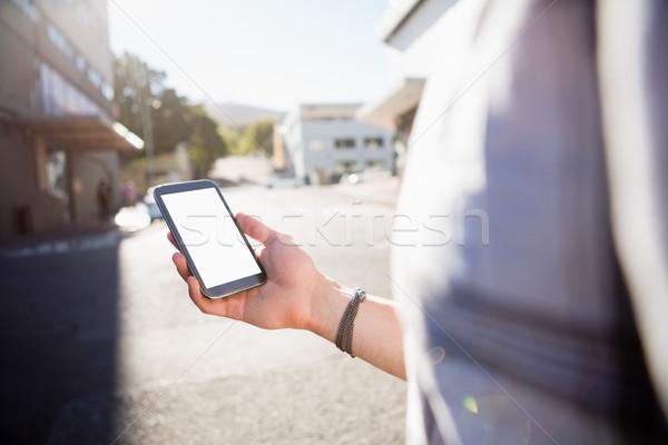 Man using smart phone while standing on city street Stock photo © wavebreak_media