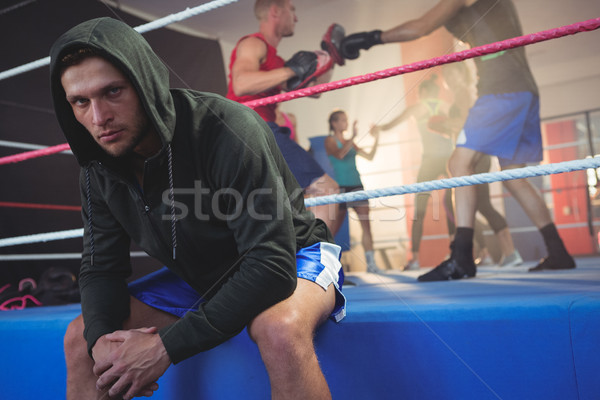 Portrait of young male boxer sitting on boxing ring at fitness studio Stock photo © wavebreak_media