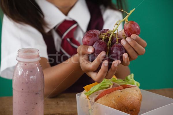 Schoolgirl having grape fruit Stock photo © wavebreak_media