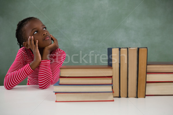Schoolgirl sitting beside books stack against chalkboard Stock photo © wavebreak_media