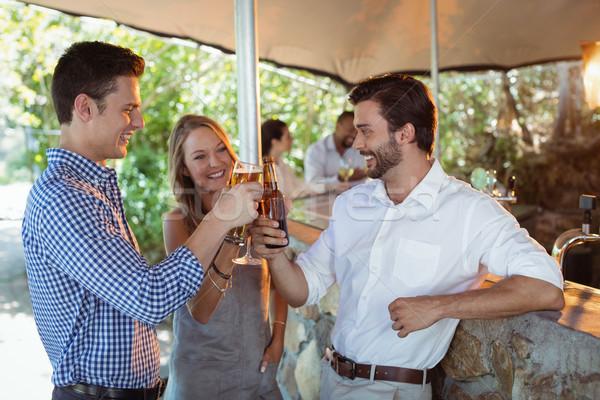 Barátok pirít üveg üveg alkohol pult Stock fotó © wavebreak_media