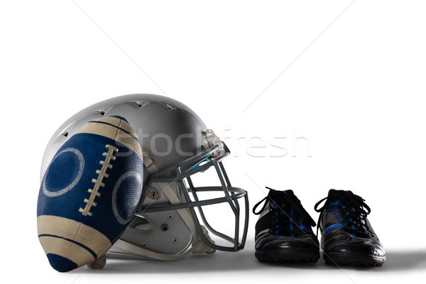 Close up of America football and helmet by sports shoes Stock photo © wavebreak_media