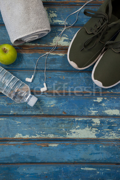 Directly above view of sports shoes and napkin by headphones with water bottle Stock photo © wavebreak_media