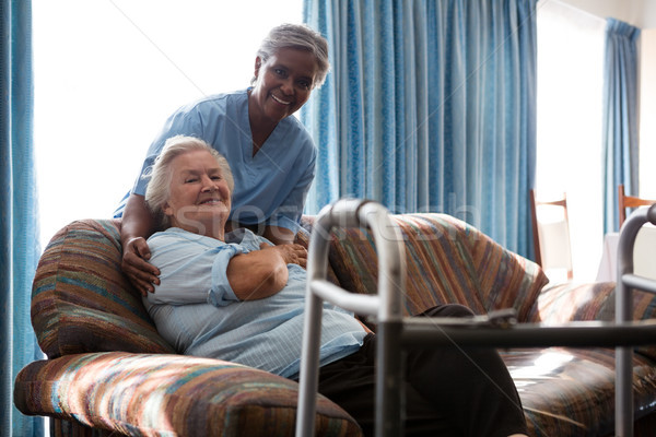 Smiling nurse with senior woman at sofa in nursing home Stock photo © wavebreak_media
