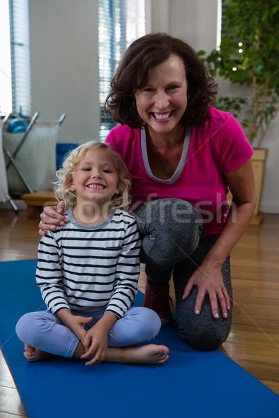 Portrait of smiling girl and physiotherapist on yoga mat Stock photo © wavebreak_media