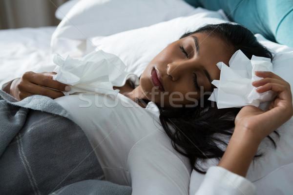 Sick woman with tissues sleeping on bed Stock photo © wavebreak_media