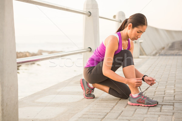 Fit woman tying shoelace at promenade Stock photo © wavebreak_media