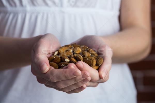 Woman showing handful of almonds Stock photo © wavebreak_media