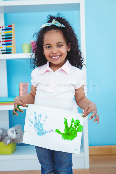 Cute girl showing paper with colored hands prints on it Stock photo © wavebreak_media
