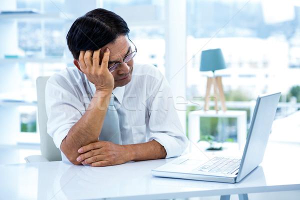Fatigué asian affaires regarder portable bureau Photo stock © wavebreak_media