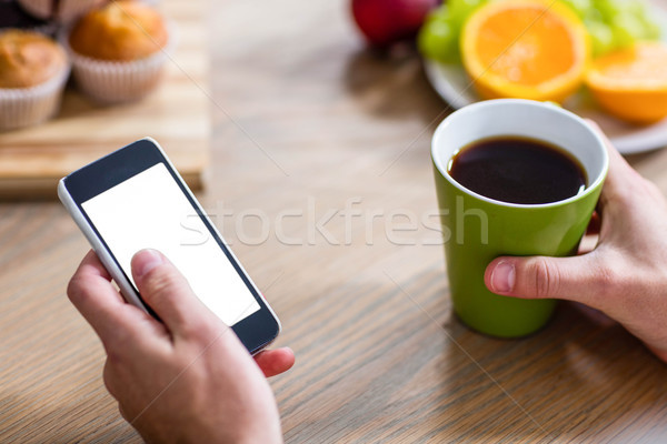 Handsome man using smartphone and holding cup Stock photo © wavebreak_media