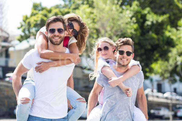 Hip men giving piggy back to their girlfriends Stock photo © wavebreak_media
