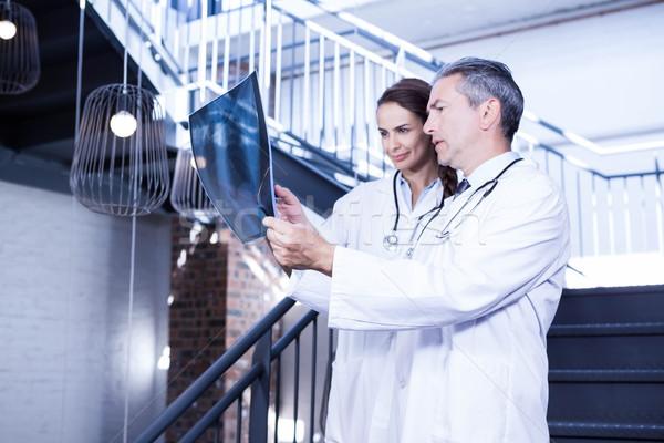 Doctors examining a x report on staircase Stock photo © wavebreak_media