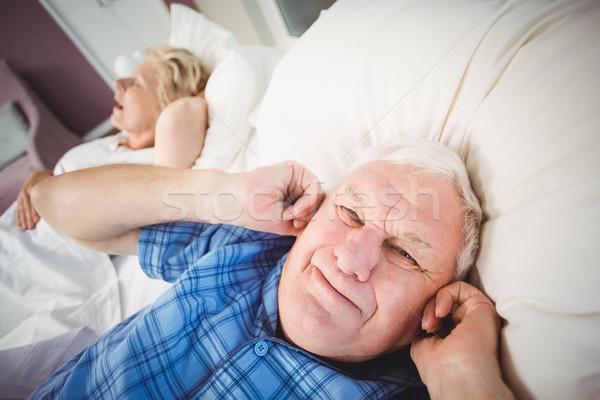 Portrait of man covering ears from snoring wife Stock photo © wavebreak_media