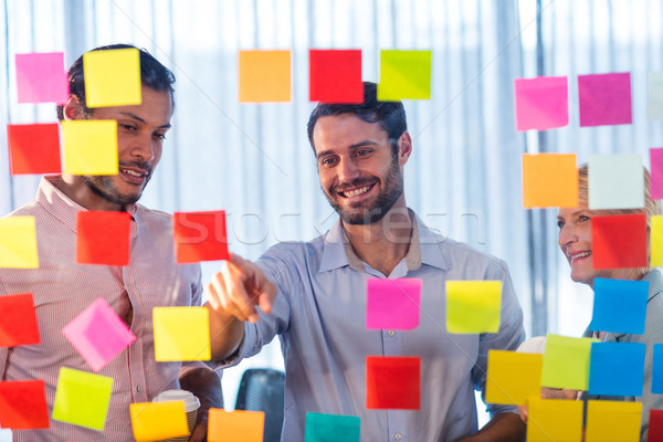 Business people looking at post it on the wall Stock photo © wavebreak_media