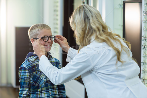 Female optometrist prescribing spectacles to young patient Stock photo © wavebreak_media