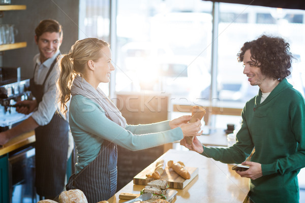 Waitress giving parcel to customer at counter Stock photo © wavebreak_media
