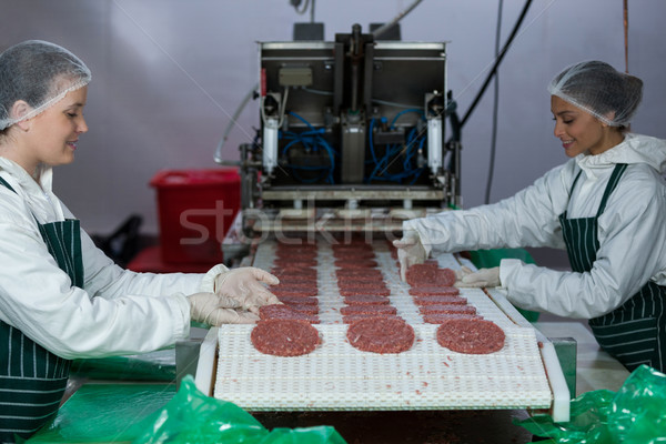 Female butchers processing hamburger patty Stock photo © wavebreak_media