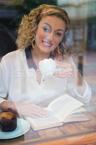 Woman having coffee while reading book seen through cafe window Stock photo © wavebreak_media