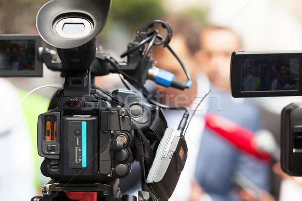 Video camera in focus, blurred spokesperson in background. Press conference Stock photo © wellphoto