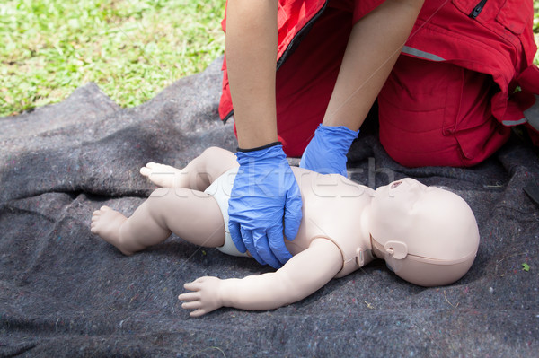 Paramedic demonstrate Cardiopulmonary resuscitation (CPR) on baby dummy Stock photo © wellphoto