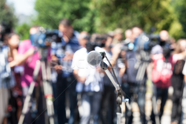 Press conference. Microphone in focus, blurred camera operators  Stock photo © wellphoto