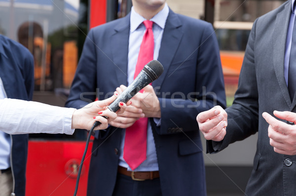 Journalist holding microphone conducting media interview. Press  Stock photo © wellphoto
