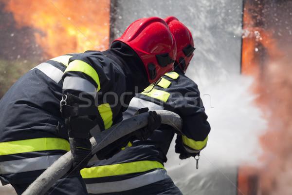 Brandweerlieden actie opleiding dienst vlam helm Stockfoto © wellphoto