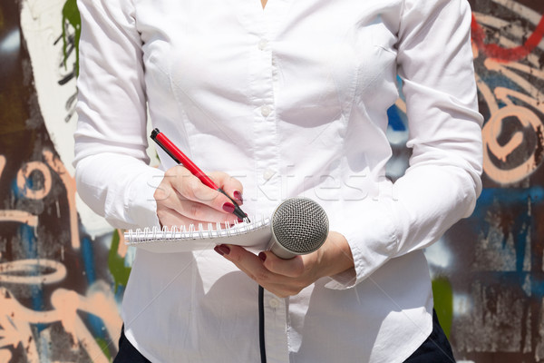 Female journalist at news event, writing notes, holding micropho Stock photo © wellphoto