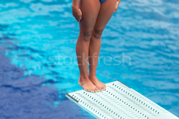 Girl standing on a springboard, preparing to dive Stock photo © wellphoto