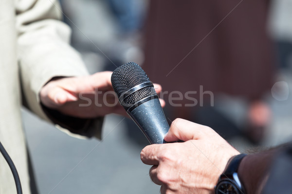 Journalist holding a microphone conducting an TV or radio interv Stock photo © wellphoto
