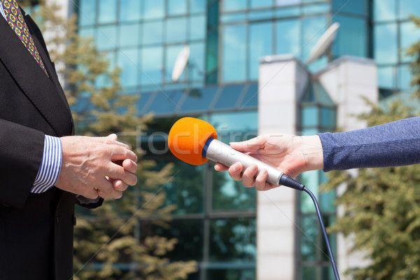 Reporter interviewing businessman, corporate building in background Stock photo © wellphoto