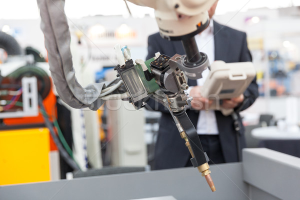 Industrial welding robotic arm, blurred operator in the background Stock photo © wellphoto