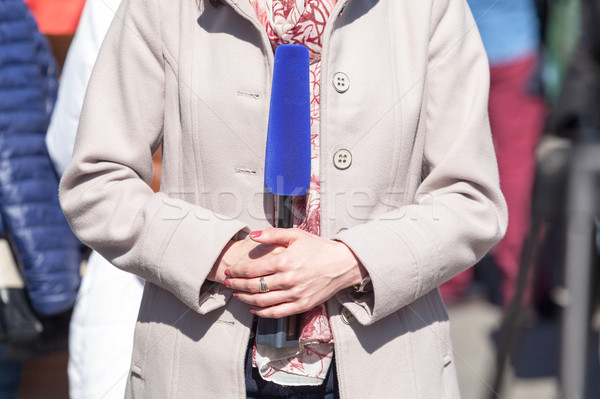 Female journalist holding microphone, reporting at a media event Stock photo © wellphoto