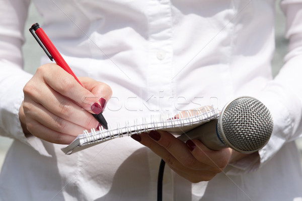 Stock photo: Female journalist at news conference, writing notes, holding mic