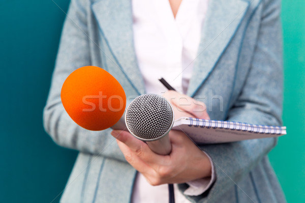 Female journalist at news conference, writing notes, holding microphones Stock photo © wellphoto