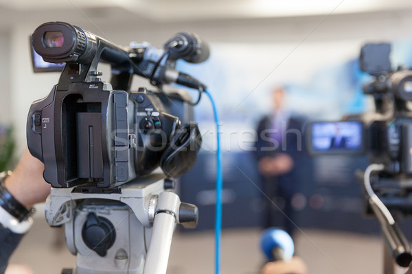 Video camera in focus, blurred spokesman in background Stock photo © wellphoto