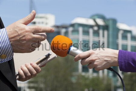 Journalist interviewing businessperson, corporate building in ba Stock photo © wellphoto
