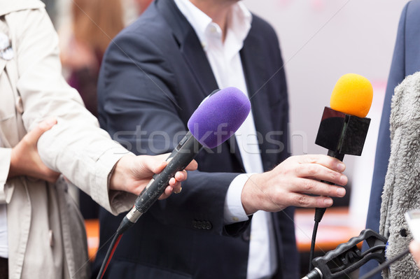 Reportes holding microphones, conducting media interview Stock photo © wellphoto
