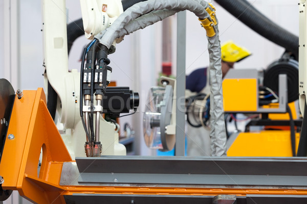 Industrial welding robot arm in the focus, blurred welder in the background Stock photo © wellphoto