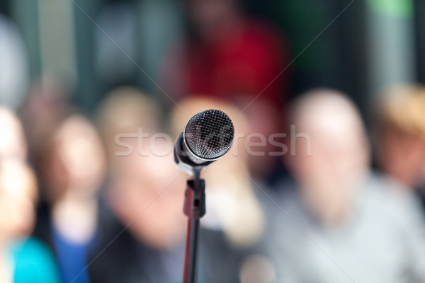 Microphone in focus, blurred audience in background Stock photo © wellphoto