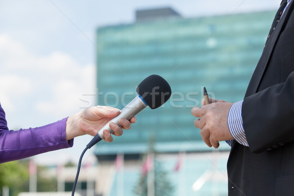 Female journalist interviewing businessman, corporate building in background Stock photo © wellphoto