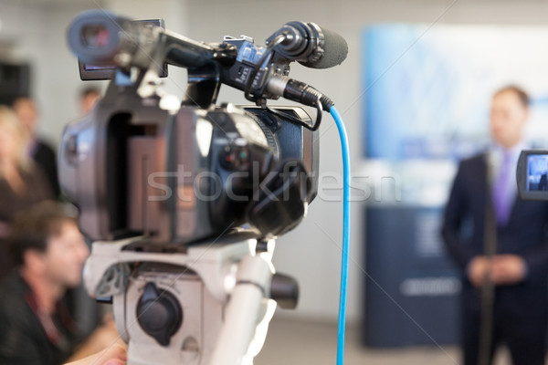 Video camera in focus, blurred spokesperson in background Stock photo © wellphoto