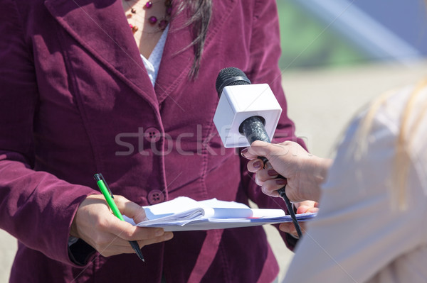 Female reporter holding microphone, interviewing woman Stock photo © wellphoto