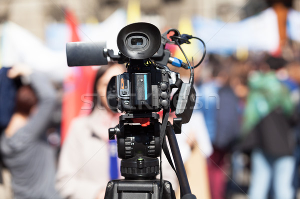 Filming female reporter with a video camera, blurred crowd in th Stock photo © wellphoto