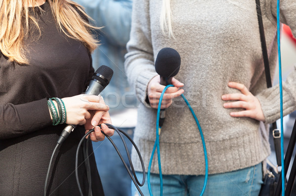 Female reporters holding microphones waiting for news conference Stock photo © wellphoto