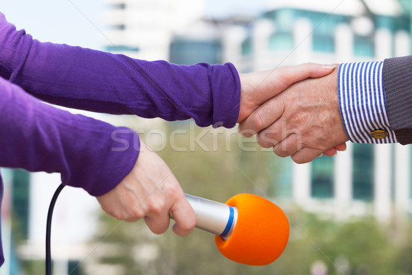 Businessman and a female reporter shaking hands before media int Stock photo © wellphoto