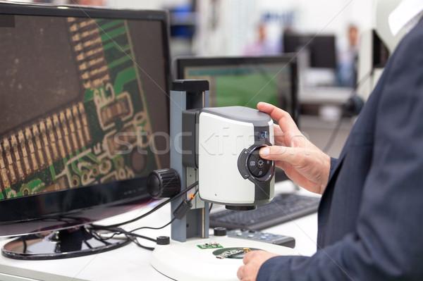 Operator working on digital microscope inspecting electronic co Stock photo © wellphoto