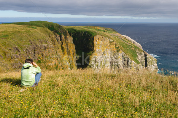 Stock photo: Birdwatcher looking at birds on Coastal Cliffs