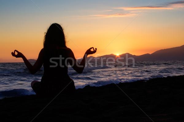 Meditando praia silhueta jovem mulher sol Foto stock © winterling